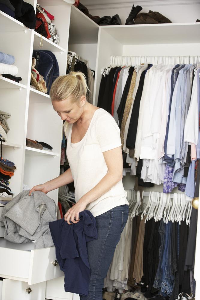 Teenage Girl Choosing Clothes From Wardrobe In Bedroom