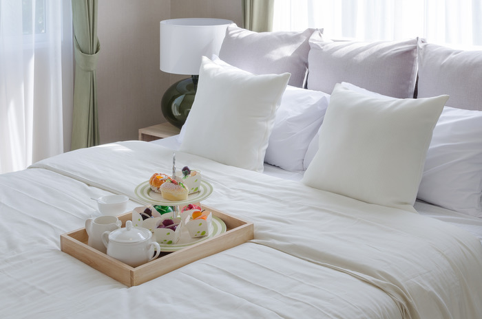 wooden ray of tea set and cup cake on white bed in modern bedroom